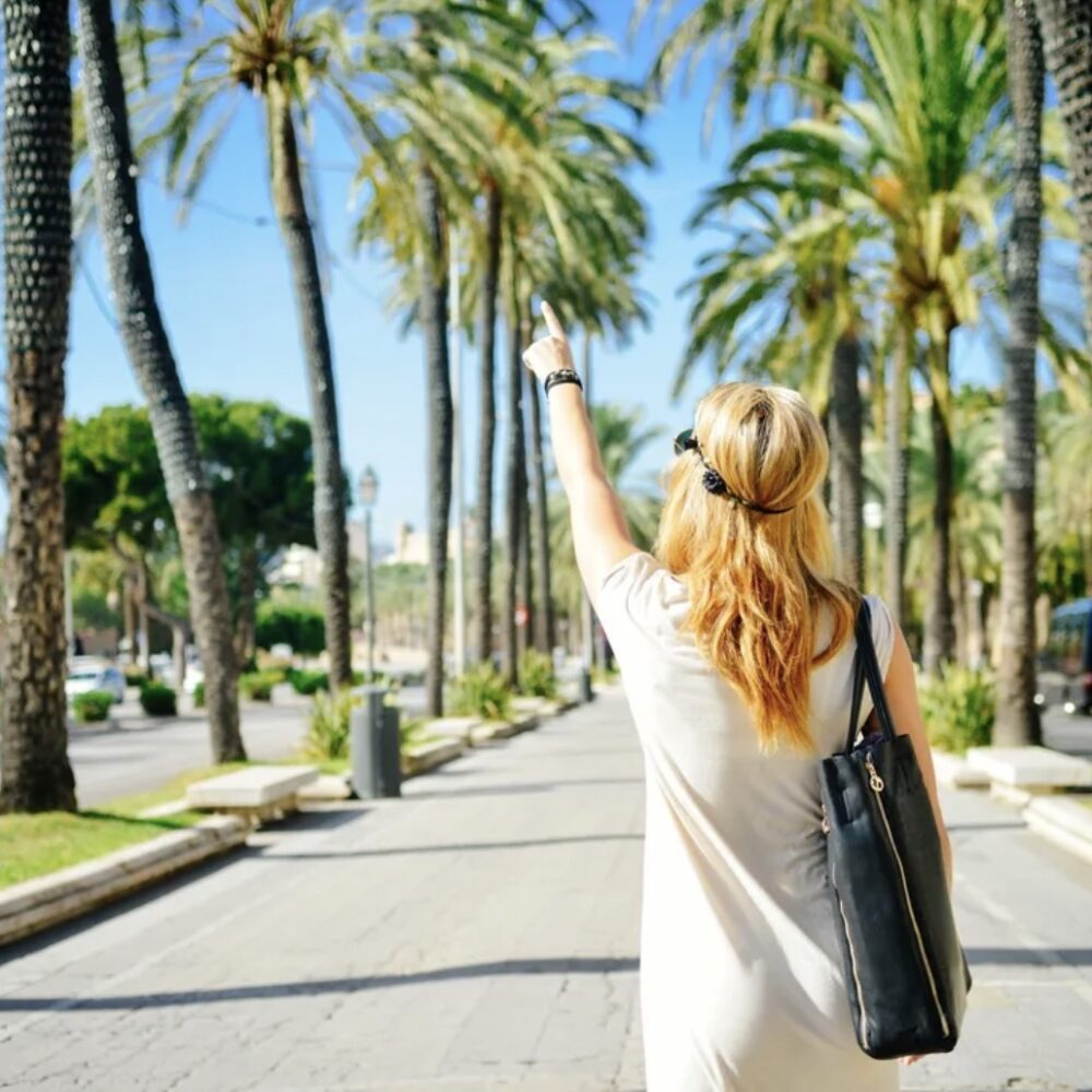 woman walking on road pointing at palm trees