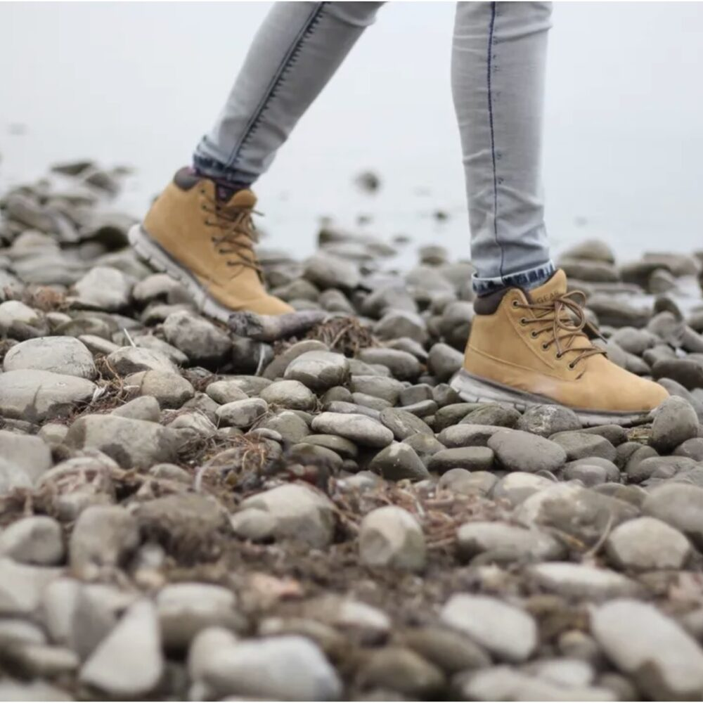 hiking boots walking on stones by ocean