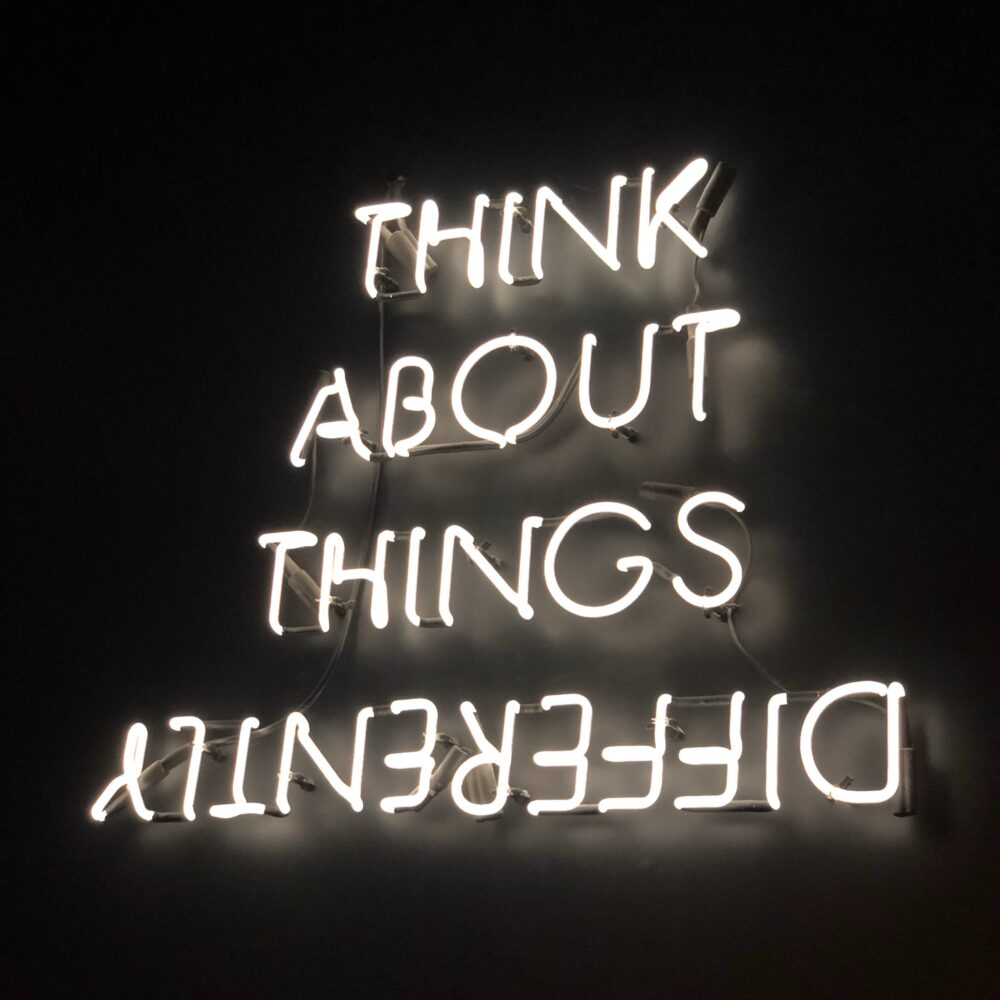 Neon sign: think about things differently, with the word Differently upside down