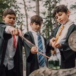 3 young wizards pointing their wands at a potion